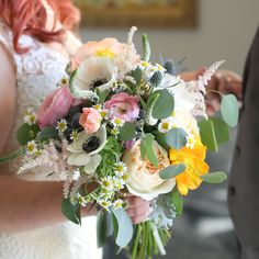 The beautiful bridal bouquet that I carried on my wedding day. The flowers included are ranunculus, poppies, anemones, chamomile, white veronica, pink astilbe, silver brunia balls, garden roses, blue thistle, dusty miller, and eucalyptus. Spring pink, peach, blush, and navy flowers in a bohemian garden wildflower arrangement.