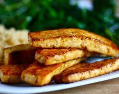 500 g de tofu extra firme, cortado em fatias finas 2 colheres (sopa) de óleo de gergelim 2 colheres (sopa) de molho de soja (shoyu) 1 colher (sopa) de vinagre de arroz 3 colheres (chá) de xarope de bordo 1 colher (chá) de molho de pimenta  1 pitada de alho em pó 1 pitada de cebola em pó 1 pitada de sal marinho  Pré-aqueça o forno a 200º C. , misture todos os ingredientes (exceto o tofu). Molhe cada fatia de tofu nos ingredientes do molho. Asse por cerca de 30 minutos