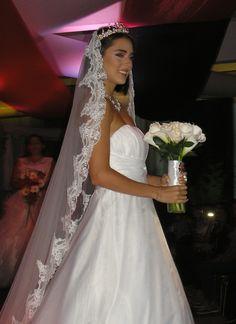 Novia de Casa de Bodas exhibiendo el bouquet en rosas blancas y mini calas.
