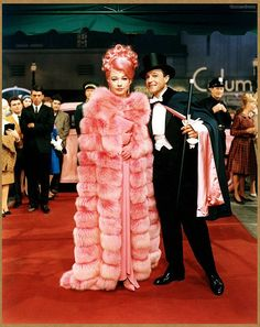 """Shirley MacLaine making an entrance, with pink hair and wearing pink chinchilla, in a scene from """"What a Way to Go"""" 1964 - Gene <3"""