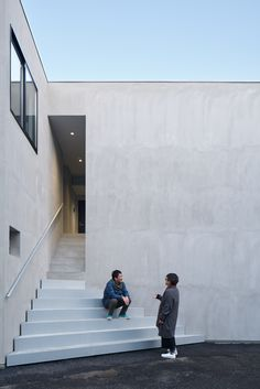 Two Apartments Across the Park is a minimalist apartment located in Chiba, Japan, designed by SO&CO. The exterior consists of a raw concrete facade with a triangular staircase leading to a small alleyway entrance hidden from view. The interior contrasts against the exterior by utilizing warm materials and light wooden floors. For each loft, the wooden floors extend upward to the wall furthest from the entrance.