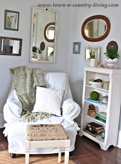 Comfy chair and vintage mirrors in the family room - www.town-n-country-living.com