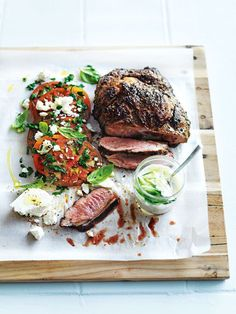 {Char-grilled lamb shoulder with tomato and feta salad.}