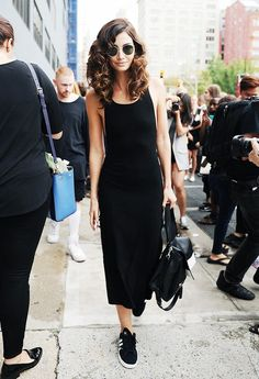 Lily Aldridge wears a LBD, black leather backpack, round sunglasses, and Adidas sneakers