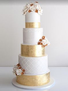 white and gold luxury wedding cake with copper flowers