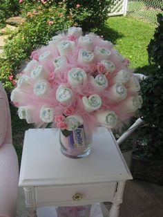 """A Diaper Bouquet. Diapers as the """"flowers"""" with some tulle (maybe tutus?) and the case filled with misc products."""