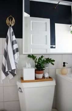 Use narrow vanity trays on top of your toilet if you don't have countertop space. | 14 Clever Ways To Declutter And Decorate Using Trays