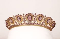 A lighter shade of amethysts used in this tiara, First Empire style, but made in the mid 19th C. Featuring nine oval amethysts, set within gold lattice open work, with smaller amethyst spacers.