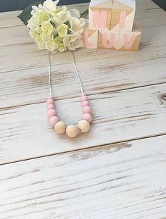 This pink nursing necklace will keep your little one entertained for hours- a great distraction for those restless, inquisitive and curious babies while feeding!  This environmentally friendly necklace is made from 100% food-grade silicone beads and natural untreated eco wood. The necklace is complete with a strong 60cm satin nylon cord and features a safety breakaway clasp, designed to pop open when pulled and tugged on. Nursing Necklace, New Mums, Teething, Food Grade, Cord, Safety, Pink, Satin, Strong