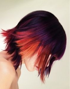 Dark medium length layered razor cut with shorter sides and bangs with dip dyed red and yellow ends hairstyle