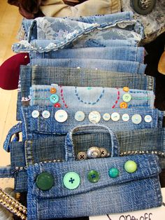 Recycled denim made into cute little purses with decorative stitching and buttons.