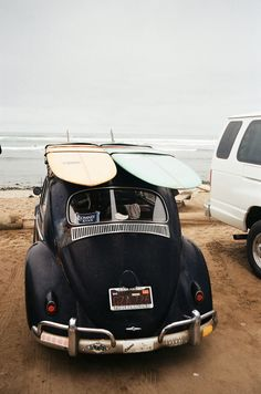Surfboards on the roof of a vintage car.  Shop our beachwear matthewwilliamson.com
