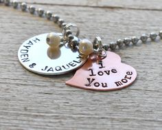 """I love you.""  ""I love you more."" One circle sterling silver disc is stamped with the 2 names of your choice.  And a copper heart is stamped with the words ""I Love You More.""  the rusted chain"