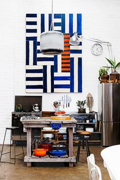 Industrial boho warehouse in Sydney furnished on a shoestring from cleverly upcycled items. Take a look round this kitchen space that has a splash of colour in the wall art and various other pieces!