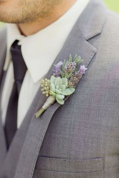 a grey wedding suit with a succulent and lavender boutonniere and a black tie looks wow