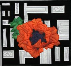 A red poppy is combined with a black and white pieced abstract background - an art quilt by Barbara Barrick McKie