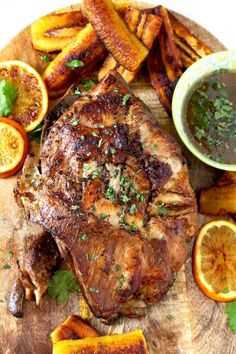 """Top view of golden and crispy Slow Cooker Cuban Mojo Pork sitting on a wooden board. Next to it is a small bowl filled with the cooking """"mojo"""" juices, golden fried plantains and caramelized orange slices. Garnished with chopped cilantro."""