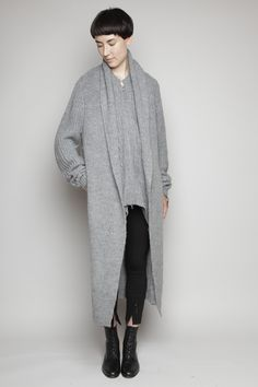 Oversized knitted wool coat with attached scarf. Layered hood with underlaying wrap scarf meant to fit over head. Dual front zip closure with long back. Long sleeves with ribbed neck, cuffs and hem. Dry clean.