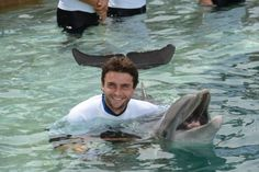Gilles Simon of France swims with a dolphin at the Miami Seaquarium's Dolphin Harbor during the Sony Ericsson Open.  March 2012.  #tennis
