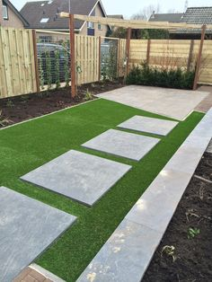Eind resultaat tuin met kunstgras en grote tegels.