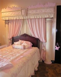 Bella Design Team created this sweet princess headboard surround. The columns and the header were made out of styrofoam - a special shop cut it to their specs. It was painted with water-based paints and covered with fabric. The fabric and upholstery nails match the bedding. The headboard surround was glued to the wall. The curtains are hanging from a rod - which was attached to the wall.