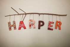"""threadpaperscissors: DIY Letters on a Branch This is so much cuter than just sticking up letters on a wall! Just stop by your local craft store: get some twine, cardboard or wooden letters, modpodge scrapbook paper/fabric on the letters and hang them from a branch! I found this photo on Onto Baby and it was made for a nursery BUT you could hang this is your living room with words such as """"family"""" or """"home"""" and it would look just as good!"""