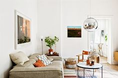 Stockholm apartment in eclectic, earthy style with Tom Dixon mirror ball pendant, photograph prints, and woven details.