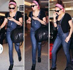 Nina Dobrev traveling (wearing: a pink bandana, black t-shirt, denim overalls, black purse and boots)