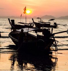 A boat is pictured on a beach as a sunset paints the sky red at Ao Nang Beach in Thailand