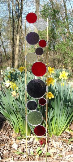 """Stained glass garden art stake in red, purple and clear textured transparent glass with solid brass frame. The glass section is 24"""" and the legs are"""