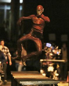 Pin for Later: Here Are Set Pictures of the Flash/Arrow Crossover!  Grant Gustin clicks his heels in his Flash costume.