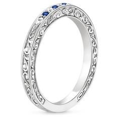 This beautiful antique-style ring is engraved with delicate scrolls that wind around the top and sides of the band. Sapphires and diamonds adorn the band for eye-catching sparkle.
