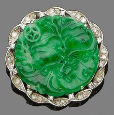 A jade and diamond brooch, the circular carved jade plaque within a single-cut diamond twisted border