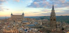 Panoramic skyline view of Toledo, Spain at sunrise: The Alcázar on the left and Cathedral on the right dominate the skyline.