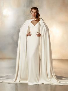 Sleek, minimalist crepe dress with asymmetrical cuts, V-neck, beaded straps that cross in back, and dramatic cape with brooch closure.