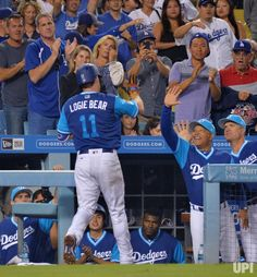 Los Angeles Dodgers' Logan Forsythe high fives manager Dave Roberts after hitting a solo home run to tie the game in the fourth inning…