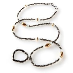 Our Hematite Necklace has been designed to provide modern day professionals an easy and stylish way to store their eyeglasses when not in use. The entire piece is strung with tiny hematite beads along with clear round beads and long oval gold bead embellishments. A hammered metal loop which holds your glasses completes the design.