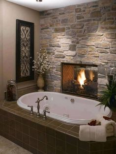 Cozy bath  - fieldstone wall and inset fireplace.