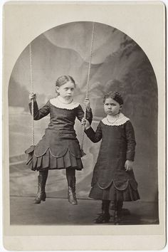 Two little girls - I'm fairy certain the child standing is deceased... I'm not sure about the one in the swing... but her eyes look painted on so I think she might be too...