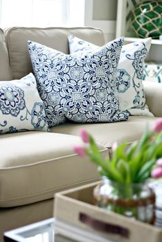 beige sofa with blue and white pillows.