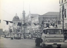 The astronauts and their party move in a motorcade through downtown Karachi enroute to the University of Karachi. Television and newsreel cameramen film the event from a truck leading the motor procession.