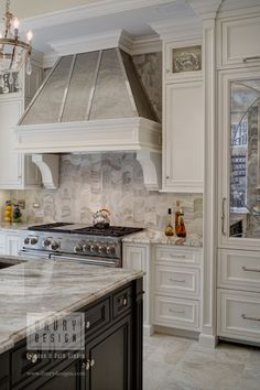 Traditional Chicago, Illinois kitchen remodel. Featuring dark stained cocoa island cabinets and super white perimeter, quartzite Cafe Latte countertops, specialty cut marble tile backsplash, custom metal range hood, SubZero & Wolf appliances, and custom eat-in breakfast nook. - By Drury Design Kitchen and Bath Studio