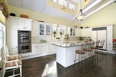 The impressive cathedral ceilings in this kitchen are illuminated by small wall sconces that help to keep the shadows away. Matching the design of the pendant light hanging from the ceiling, they may not do more than cast a soft glow over the kitchen, but the highlight the vaulted arch and windows along the ceiling.