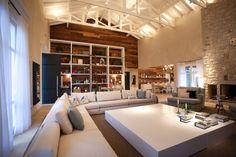 """Lareira, TV e estar estão integrados no living. Em primeiro plano, o sofá em """"L"""" Brentwood mede 4 x 4m; a mesa de centro, quadrada, em marcenaria foi desenhada pelo arquiteto Maurício Karam - responsável pela arquitetura - e tem lado com 2,4 m. A chaise longue de linho verde claro é da Artefacto (à dir.) e o tapete de algodão que dá aconchego à sala mede 7 x 7m"""
