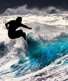 Surfer shredding a wave + art photograph + black and white + touch of blue + selective color + beach