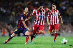 Lionel Messi of FC Barcelona duels for the ball with Arda Turan of Atletico de Madrid during the Spanish Super Cup second leg match between FC Barcelona and Atletico de Madrid at Nou Camp on August 28, 2013 in Barcelona, Catalonia.