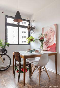 Sala de jantar com mesa de madeira, cadeira Eames, muitas plantas, iluminação pendente e quadro de ilustração.