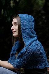 Beaded lace and garter stitch combine beautifully in this hooded shawl which is cast on in the traditional manner at bottom edge and is worked up to the top of the hood, where a single seam joins it all together. Shoulder shaping produces an excellent fit, and the garter stitch border provides a lovely resting space for a shawl pin at the neck overlap. This pattern is both written out and charted. Beads are added with the crochet hook add-as-you-go method.