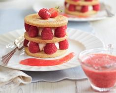 Fruit shortbread stacked with layers of creamy custard, raspberries and strawberry sauce