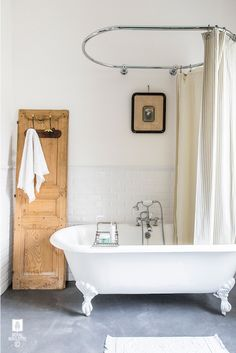 Vintage bathroom boasts upper walls painted soft white and lower walls clad in white beveled subway tiled wainscoting with oval shower rail mounted on wall dressed in gray pinstripe shower curtain over claw foot tub beside repurposed door used as a towel rack.
